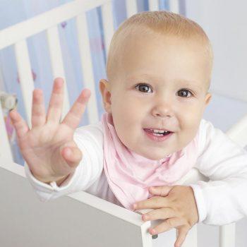 Pronto para deixar o berço - Retrato de um bebê dentro do berço que acena